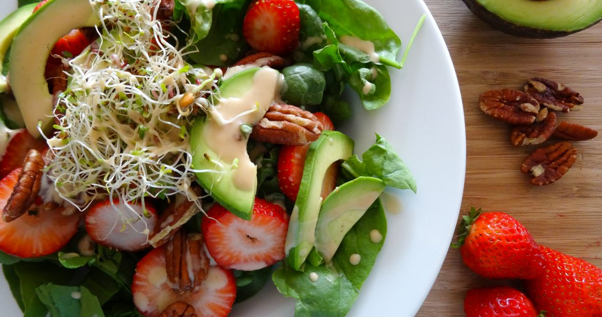overhead shot of spinach strawberry and avocado salad with sprouts and pecans on wood cutting board with white plate