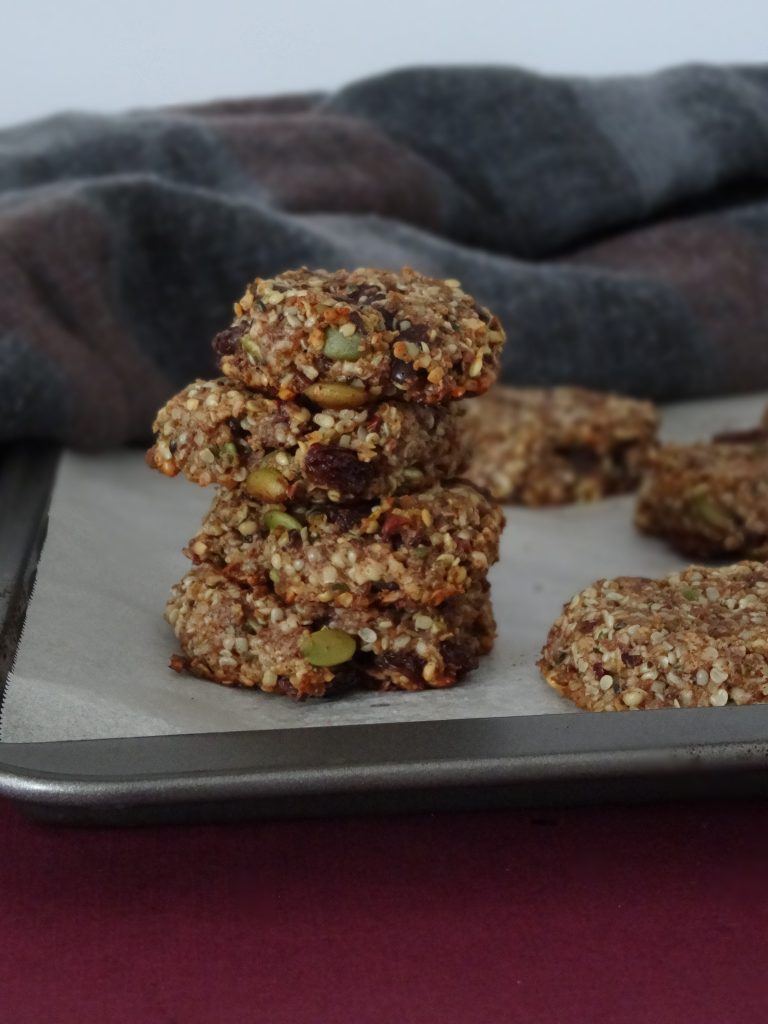 vegan seed and fruit cookies with burgundy and grey scafe on white parchment paper lined pan