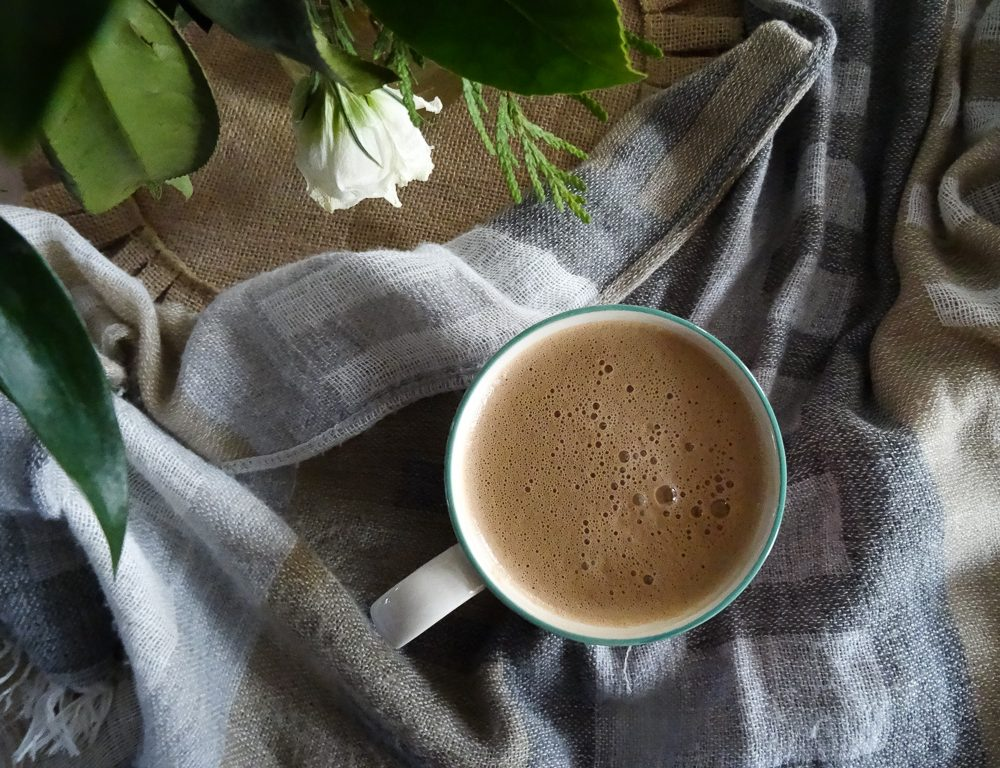 dairy free chocolate elixir with grey white scarf and green and white plant