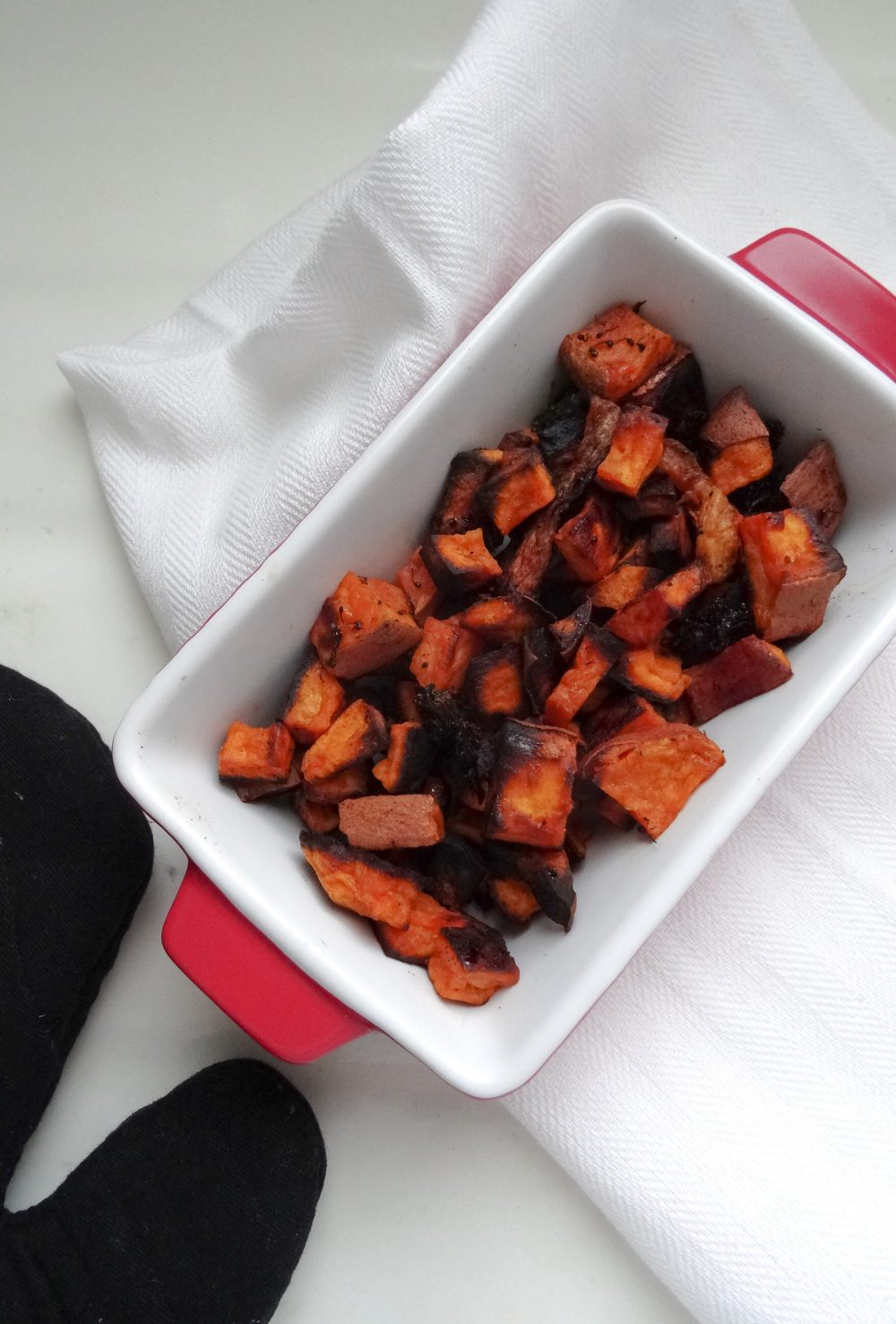 roasted yam and sweet potatoes in red ceramic dish on with white napkin
