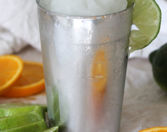 classic frozen lime margarita with lime and orange and white cloth
