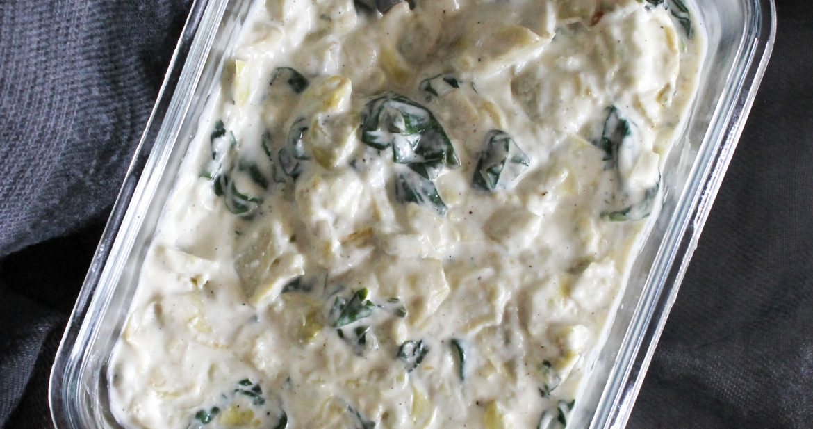 creamy dairy-free spinach artichoke dip in glass reuseable bowl with grey background