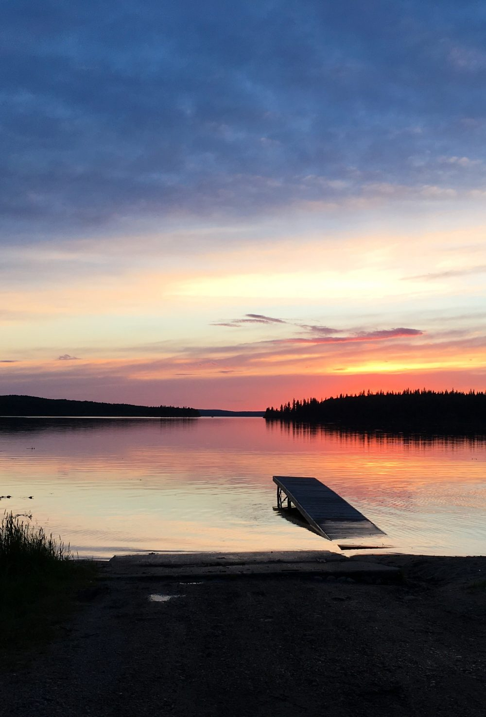 Sunset reflecting on the calm water at Pierce Lake, Saskatchewan