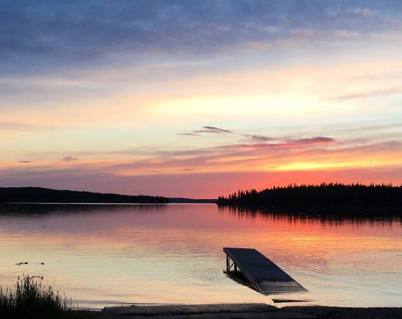 Sunset reflecting on the calm water at Pierce Lake, Saskatchewan