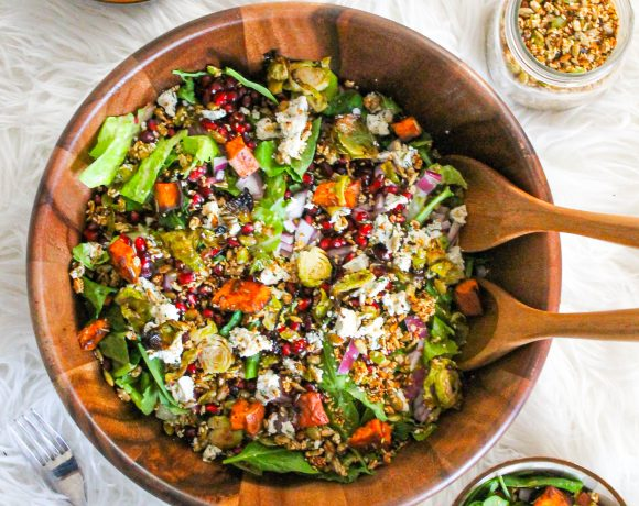 Super Harvest Salad with kale, spinach, arugula, pomegranate, red onion, roasted yams, Brussels sprouts, sesame seeds, pumpkin seeds and sunflower seeds with a creamy balsamic dairy free vegan dressing