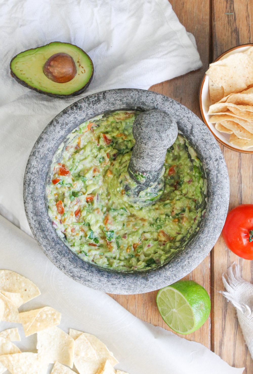 authentic guacamole with avocado, tomato, onion, lime juice, cilantro, organic corn chips in mortar and pestle