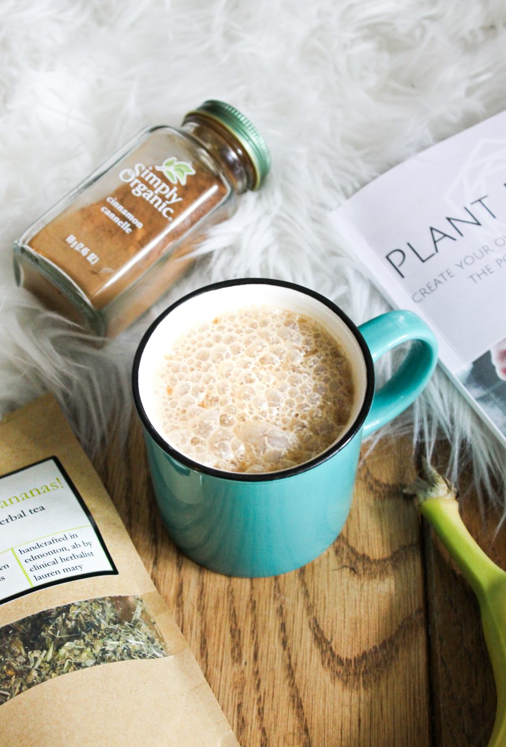 banana coconut dairy free latte in a teal mug with wood flooring and white rug with local Elle Wellness tea