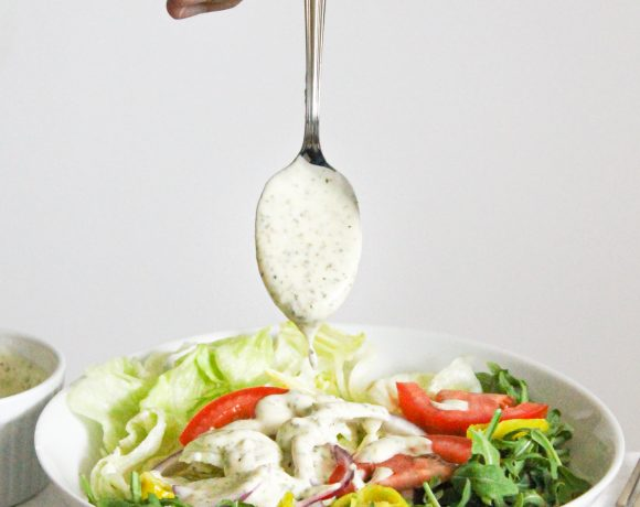 olive garden mimic salad in a white bowl with lettuce, arugula, tomato, red onion, pepperocini and homemade olive garden dressing