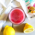 pink electrolyte lemonade made with pineapple passionfruit pink dragon fruit lemon and coconut water with white tile and white napkin