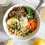 salad bowl with arugula, spinach, chickpeas, sauerkraut, red peppers, quinoa, green onions, crispy potatoes, sesame seeds on a white background with lemon dill tahini dressing